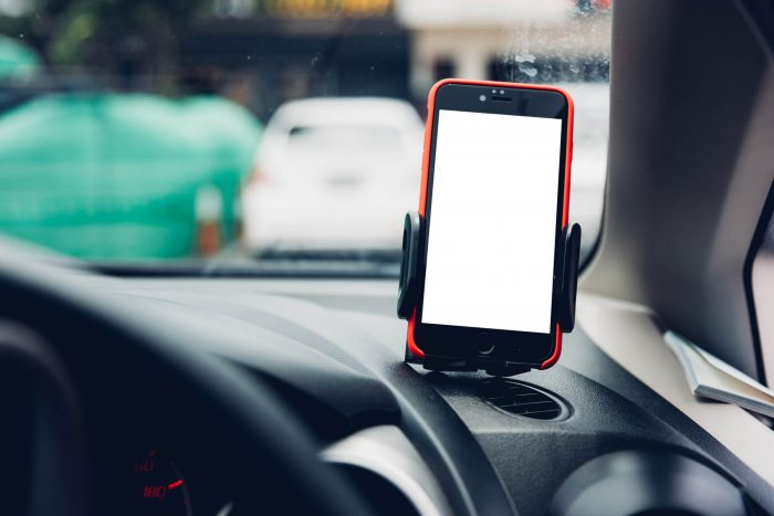 Smart phone in holder on dashboard of car