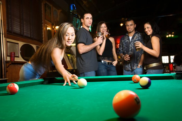 Young woman playing pool with group of friends in pub, Central Coast NSW